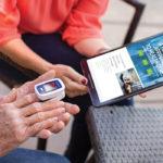 Man using an Alanté finger glucose tester with a women holding a tablet to show Alanté website