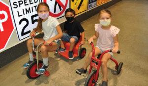 3 children riding trikes inside the Children's Museum