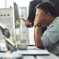Man at work stressed out as another man stands over him